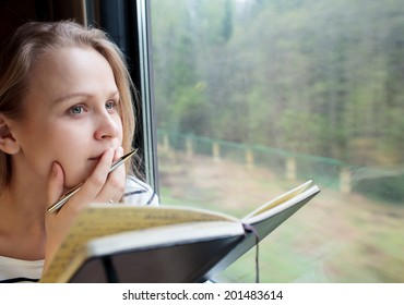 Young woman on a train writing notes in a diary or journal staring thoughtfully out of the window with her pen to her lips as she thinks of what to write
