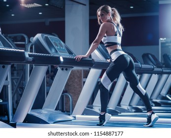 Young woman on a treadmill in the gym. Young fitness girl exercises on treadmill machine. Sports exercises for weight loss.