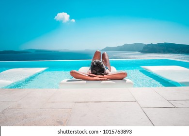 Young woman on vacation at Santorini, women at the swimming pool looking out over the Caldera ocean of Santorini, Girl at the infinity pool Oia Santorini Greece