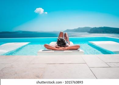 Joven de vacaciones en Santorini, mujeres en la piscina con vistas al océano de la Caldera de Santorini, Chica en la piscina infinita Oia Santorini Grecia