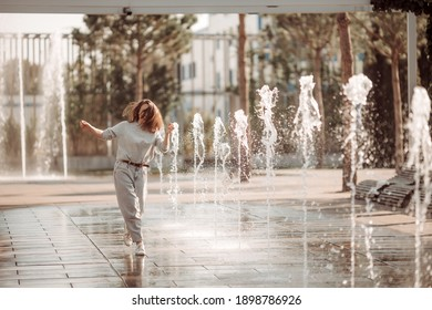 Young woman on a walk in the city by the fountains