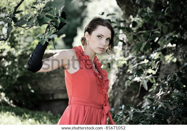 The young woman on walk in park near a tree