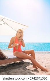 Young woman on white beach relaxing on sunbed