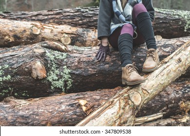 Young woman on wood logs