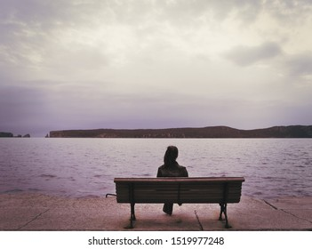 Young woman on wooden bench  at seafront  and island under dramatic sky. Vintage photo soft focus nostalgic photo effect applied.