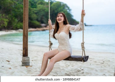 young woman on a wooden swing in the sea beach at Koh MunNork Island, Rayong, Thailand