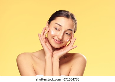 Young woman on a yellow background applies cosmetic face cream.