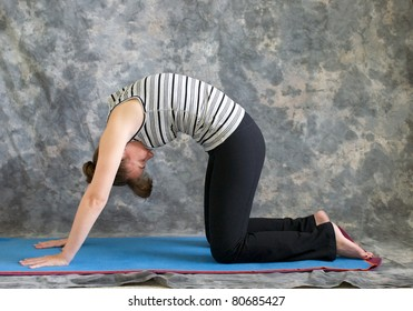 Young woman on yoga mat in  Yoga posture Marjaryasana or cat pose against a grey background in profile, facing left lit by diffused sunlight.