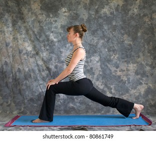 Young woman on yoga mat in woman doing Yoga posture high Lunge with hands on knee, against a grey background in profile, facing left lit by diffused sunlight.