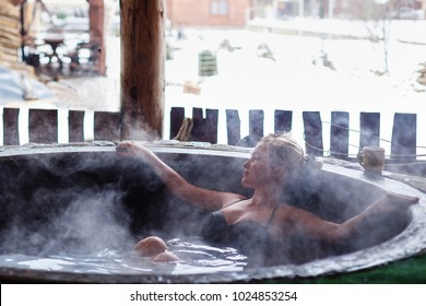Young woman in an open air bath while snowing