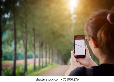 young woman open app gps at smartphone on road in the forest