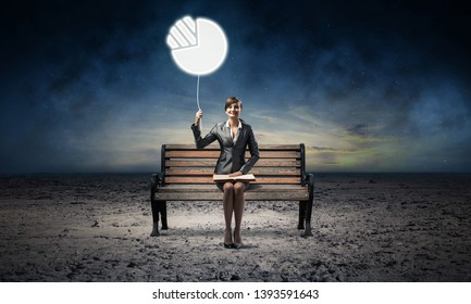 Young woman with open book on wooden bench outdoor. Pretty girl in business suit holding round financial diagram symbol. Beautiful skyscape with deep blue night sky. Business analytics and statistics