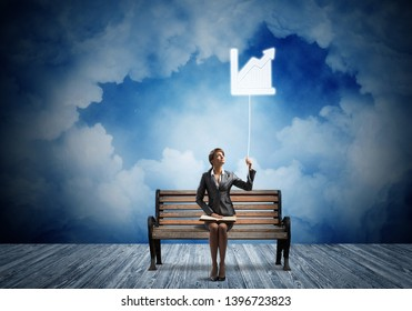 Young woman with open book on wooden bench outdoor. Pretty girl in business suit holding growing diagram symbol. Beautiful skyscape with deep blue night sky. Business analytics and statistics