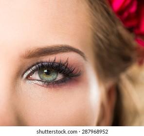 young woman open eye with makeup closeup