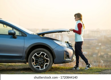 Young woman opening bonnet of broken down car having trouble with her vehicle. Female driver standing near auto with popped up hood.