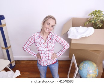 Young woman opening boxes after moving house.