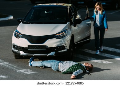 young woman opening car door and going to injured man lying on road after car accident