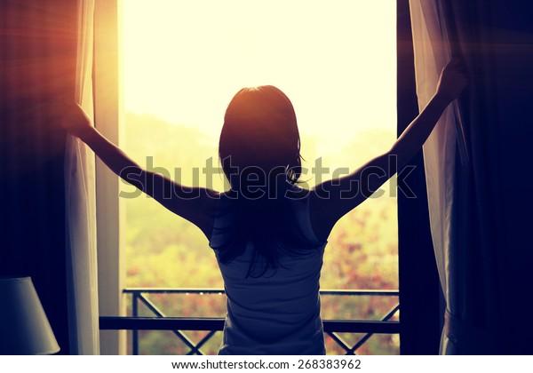 寝室でカーテンを開ける若い女性
