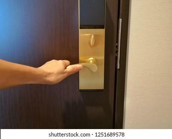 Young woman opening door with dark brown background.