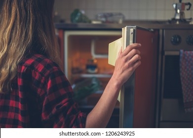 A young woman is opening the door of her fridge
