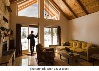 Young woman opening the door and looking through the window wall in a beautiful mountain log cabin with snowy landscape in the background.