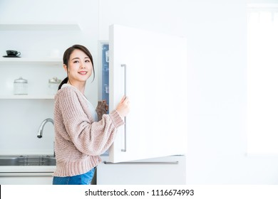 Young woman opening a door of a refrigerator.