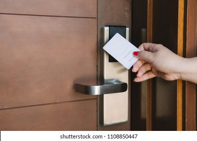 Young woman opening hotel room electronic lock with key card