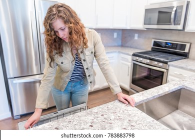 Young woman opening inspecting dishwasher in modern gray, brown kitchen features cabinets with granite countertops and tile backsplash with stove oven