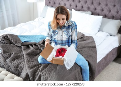 Young woman opening parcel in bedroom at home