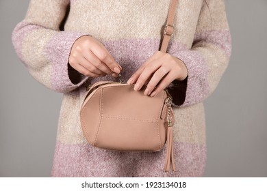 young woman opening the pink bag.