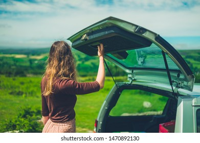 A young woman is opening the trunk of her car in nature on a sunny summer day