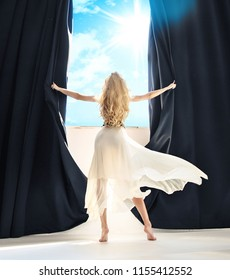 Young woman opens curtains at the window