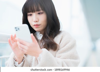 Young woman operating a smartphone