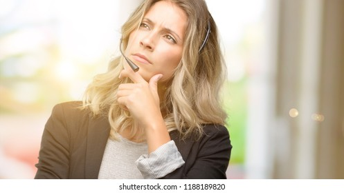 Young woman operator from call center thinking and looking up expressing doubt and wonder