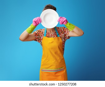 young woman in orange apron holding washed plate in the front of face isolated on blue. Perfect clean dishes - the pride of every housewife!
