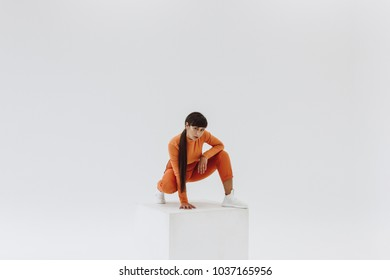 young woman in orange clothes sitting on white cube