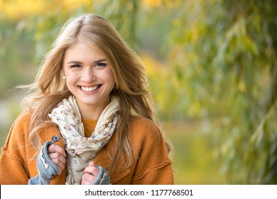 A young woman in an orange fashion coat clasps her hands to her chest. Model warms hands in knitted gloves