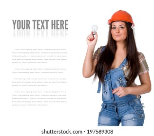 Young woman in orange helmet and jeans holding light bulb. Isolated on white.