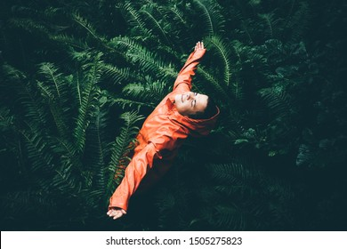 The young woman with orange raicoat smiles and laughs under the rain. Girl enjoying warm summer rain at the tropical forest. Сoncept of nature and happy life, adventure.