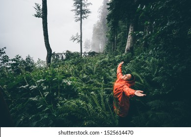 The young woman with orange raincoat smiles and laughs under the rain. Girl enjoying warm summer rain at the tropical forest. Concept of nature and happy life with adventure.