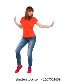 Young woman in orange shirt, jeans and red sneakers is standing with arms outstretched, pushing something and smiling. Front view. Full length studio shot isolated on white.