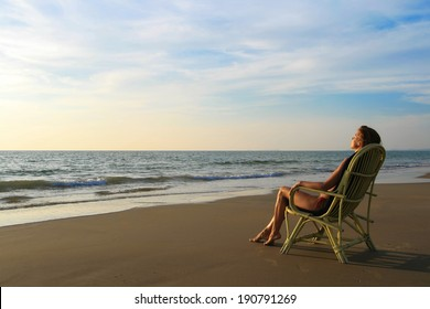 Young woman in orange swimwear sitting on the wicker chair