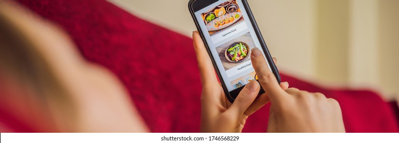 Young woman orders food for lunch online using a smartphone BANNER, LONG FORMAT