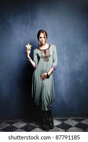 young woman in oriental dress holding flower orchid in hand, indoor shot