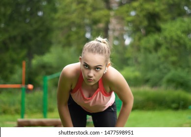 young woman is out of breath and makes a breather bent over while doing sports outdoors