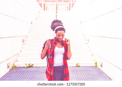 young woman outdoor in the city listening music headphones dancing - music, relaxing, enjoyment concept