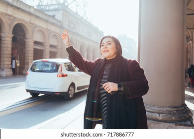 Young woman outdoor hailing a taxi - transport, car sharing, get a ride concept