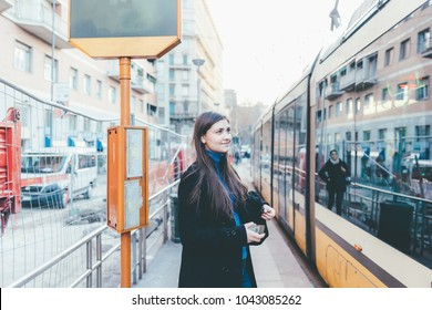 Young woman outdoor using smart phone hand hold waiting bus stop - technology, social network, commuting concept