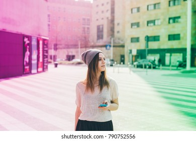Young woman outdoor using smart phone hand hold looking away - technology, social network, phubbing concept