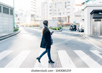 Young woman outdoor walking in the city back light holding smart phone - technology, shopping, traveler concept
